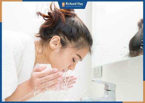 Vệ sinh vết thương bằng nước muối sinh lý và sử dụng bông tẩy trang hoặc bông gòn để rửa